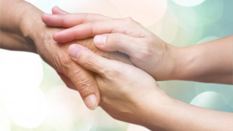 Caregiver, carer hand holding elder hand in hospice care. Philanthropy kindness to disabled concept.
