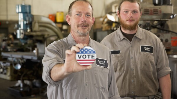 Caucasian machinists holding Vote' button in garage