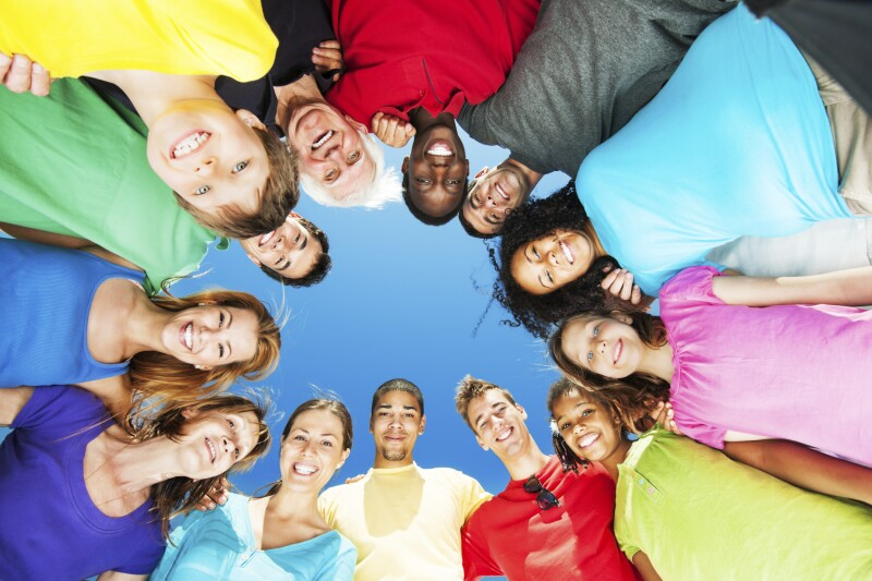 Group of embraced people standing in circle against blue sky.
