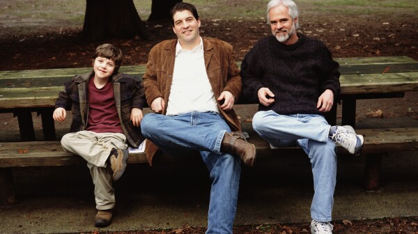 Grandfather, father and son (5-7) sitting on park bench, portrait