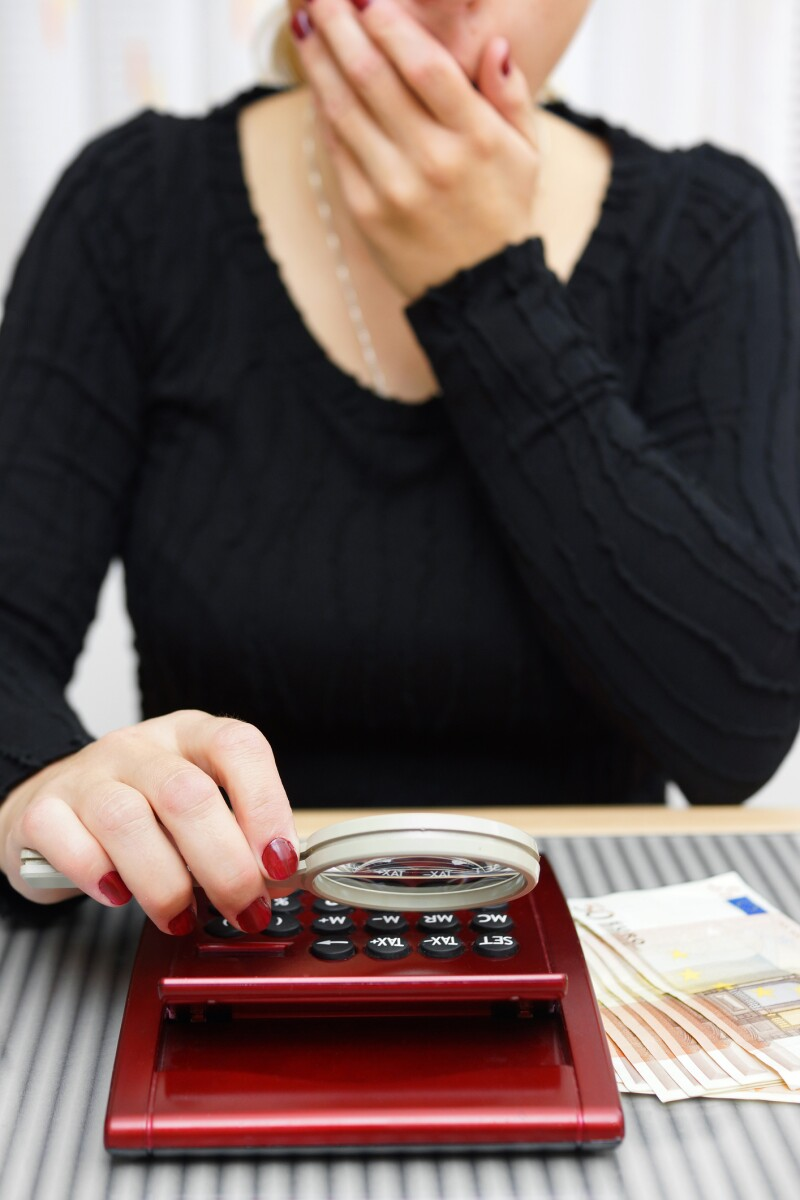 woman watching sum on calculator with magnifying glass