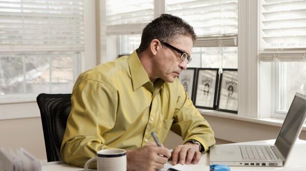 Hispanic man paying bills at desk