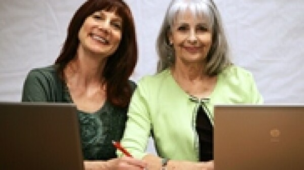 two ladies smiling with laptops