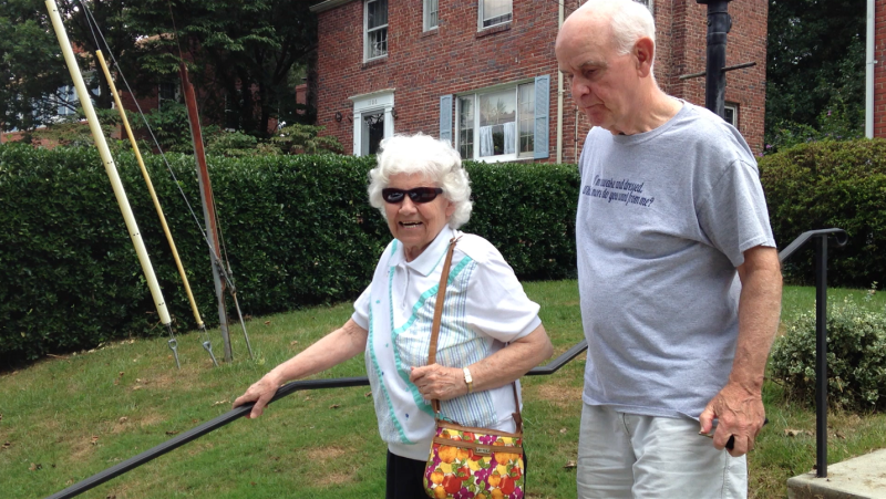 A volunteer escorts an elderly woman to his car to drive her to an appointment.