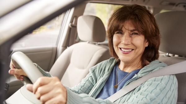 Senior woman in car driving seat looking at camera, close up