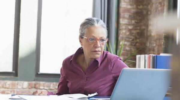 Hispanic businesswoman using laptop in office