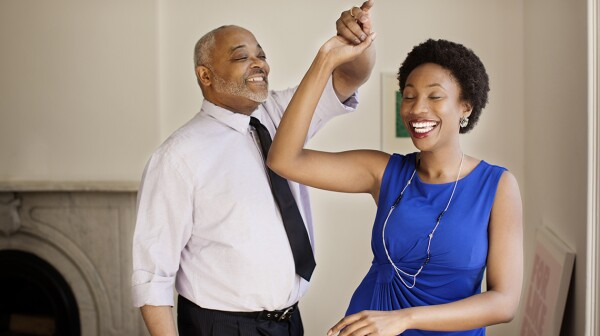 Happy daughter and father dancing at home