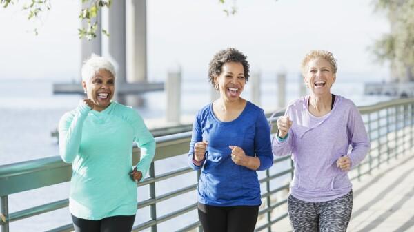 Three women running on waterfront