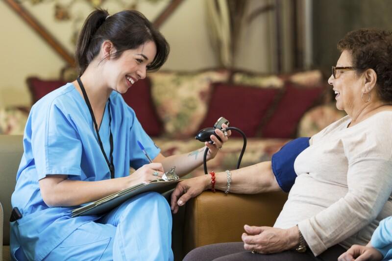 Home healthcare nurse checks patient's blood pressure