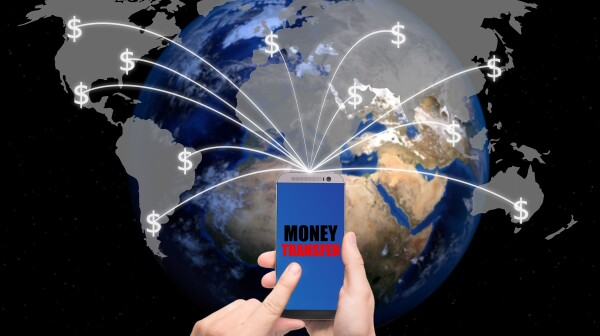 Hand holding smart phone sent money dollar bills flying away from screen to global map. Technology online banking money transfer, e-commerce concept.