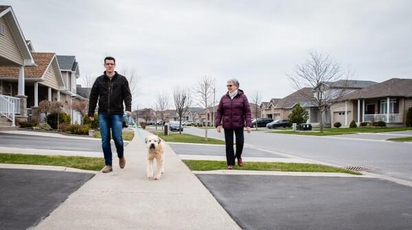 Man and older lady walking dog on sidewalk of suburban neighborhood.