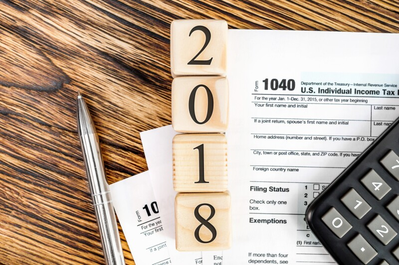 Pay tax in 2018 year concept. Numbers 2018 wit tax form 1040, calculator and pen on the table. Top view.