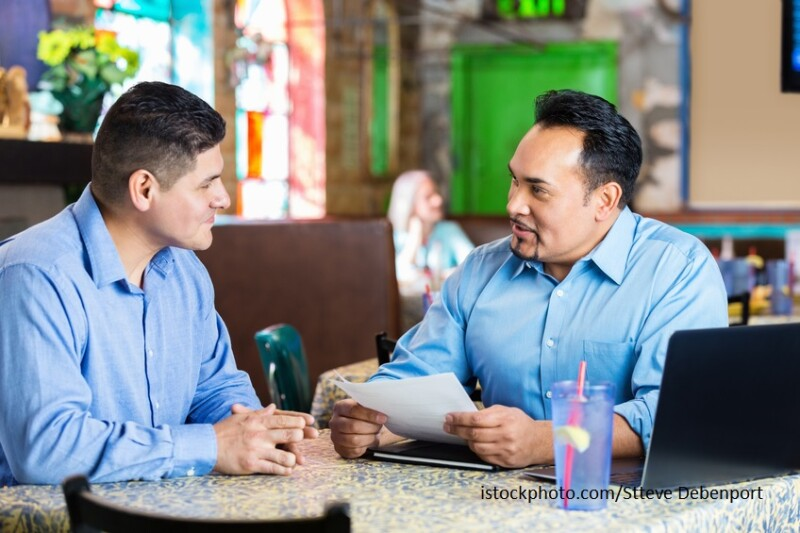 Restaurant manager interviewing Hispanic man for employment