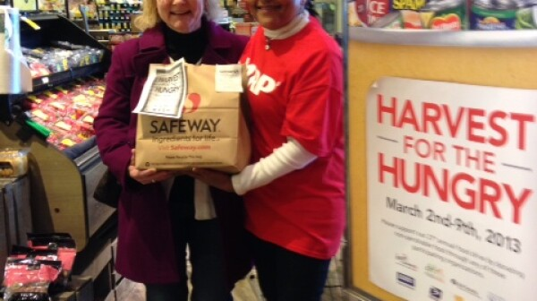 Maryland volunteer Elois stands with a customer who purchased a pre-filled bag of groceries for donation.