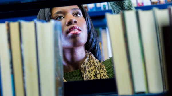 African American college student searching for library book on shelf