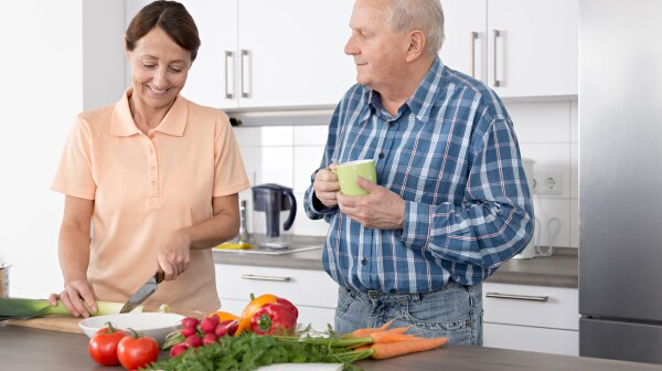 Woman caregiver chopping vegetables with an older man in a kitchen