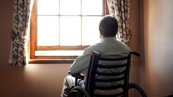Man sitting in a wheel chair in front of a window