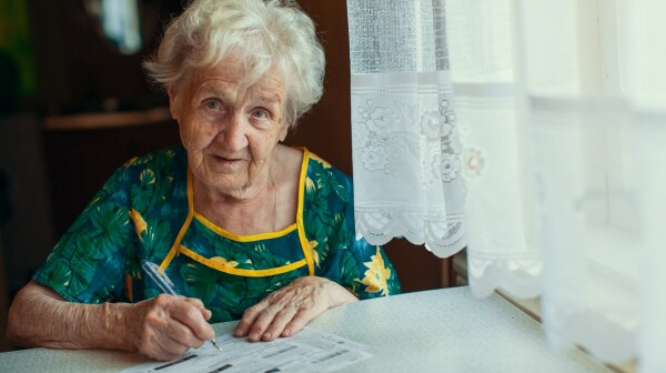 MONEY_elderly woman paying bills_DimaBerkut