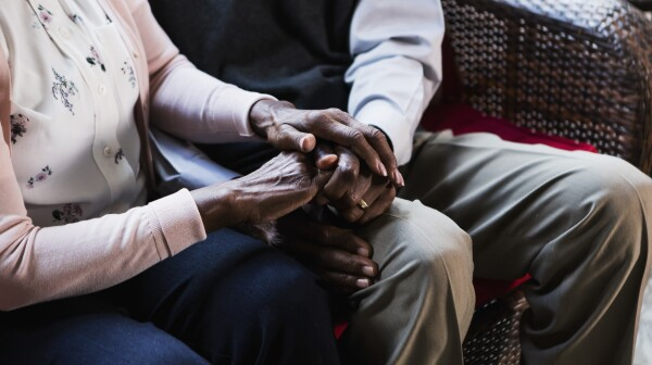 Senior African-American couple sitting, holding hands