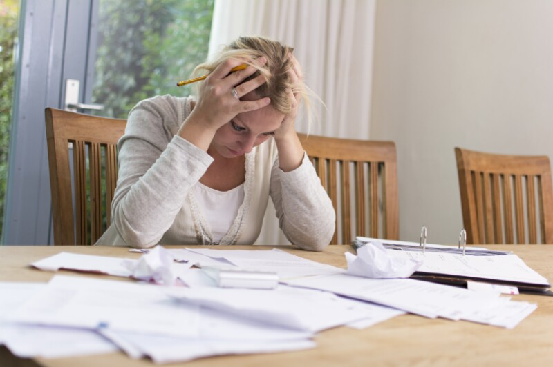 Exasperated woman at desk with paperwork_mactrunk_499.997
