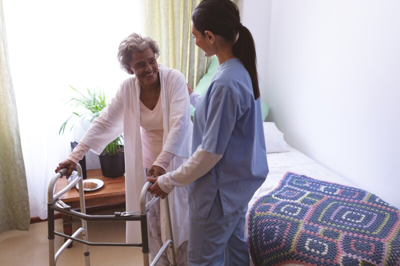 Female nurse helping senior female patient to stand with walker
