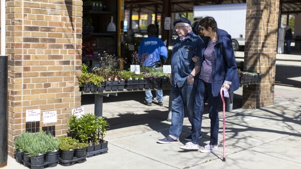 A older man and woman walk past a shop with plants for sale