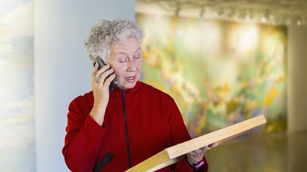 Older mixed race woman talking on phone in art gallery