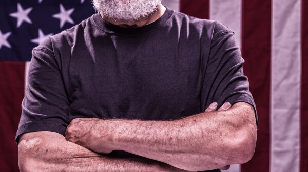 USA Vietnam Veteran With Arms Crossed and American Flag Background