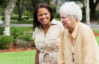 Caregiver (50s) helping senior Hispanic woman (70s) with walker outdoors.