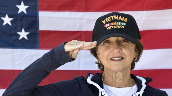 Female Vietnam Veteran Saluting  looking content wearing Veterans cap, with American Flag in background.