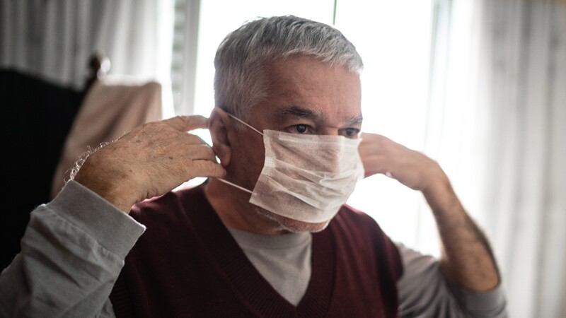 Senior man putting on a protective mask for coronavirus at home