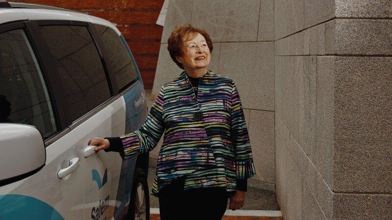 An older woman standing by a van