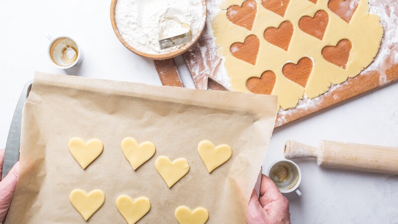 Man  making Valentines day cookies, overheard view of holiday baking