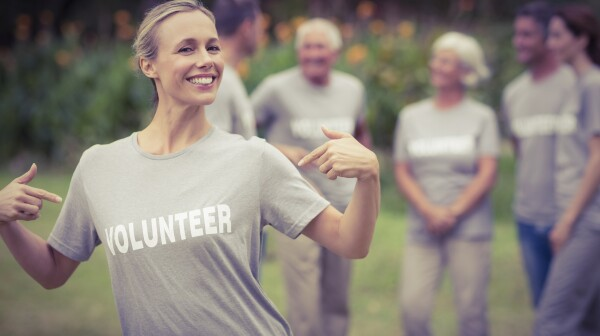 Happy volunteer showing her t-shirt to camera