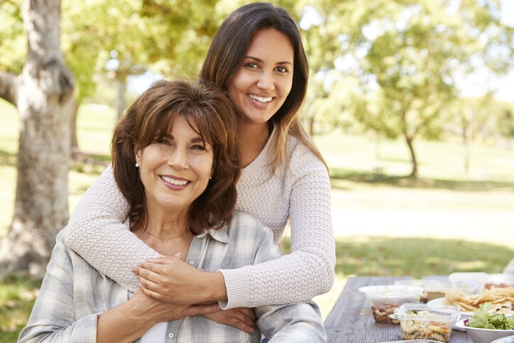 Senior mother and adult daughter embracing in park, close up