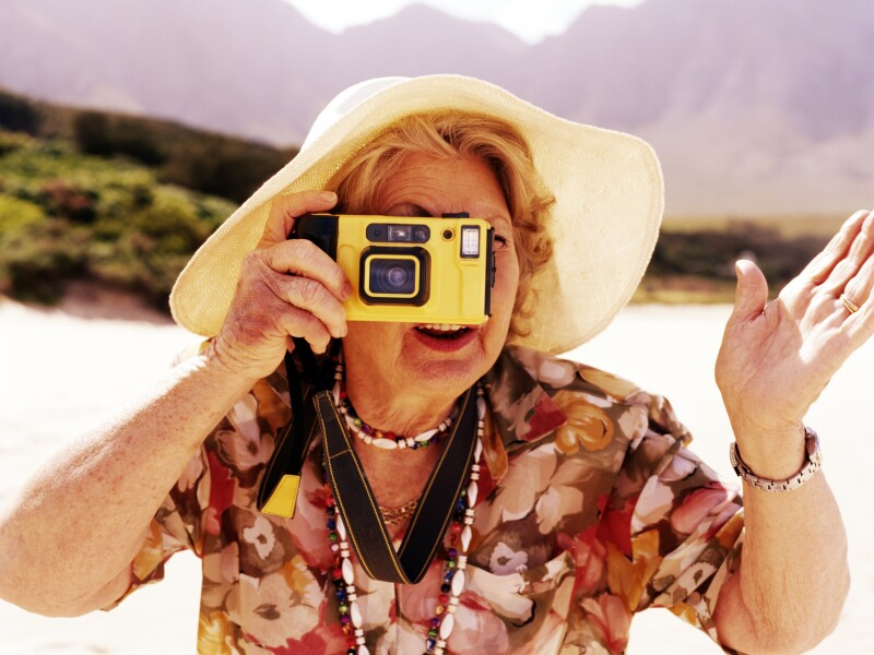 Senior woman taking photograph outdoors