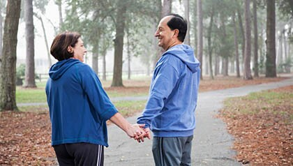 Hispanic couple walking in park