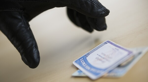 Close up of thief's hand in black glove stealing driver's license, studio shot