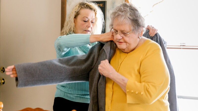 A woman helps her elderly mother put on a coat