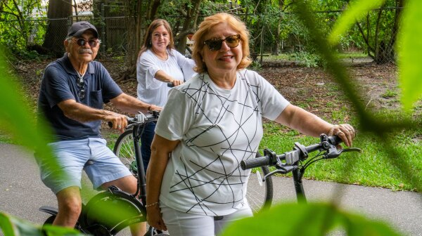 An older man and two women on bikes