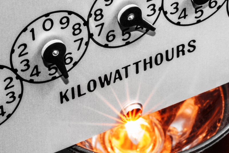 Kilowatthour electric meter register dials with light bulb shining below