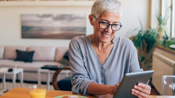 Happy woman working on digital tablet