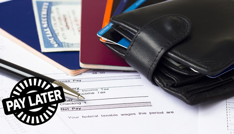 pay later stamp on top of paycheck, pay statements, wallet, pass