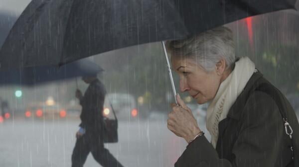 Mature woman walking with umbrella
