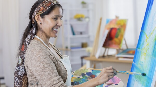 Beautiful woman paints in her art studio
