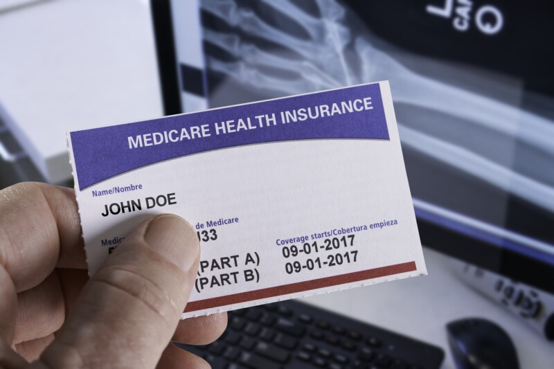 Medicare Health Insurance Card in medical office with Xray and hand holding
