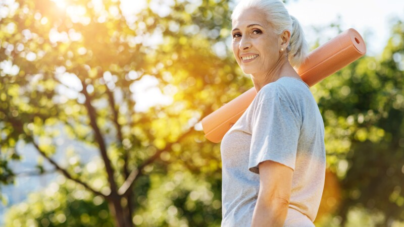 Cheerful senior woman going to enjoy yoga in the park