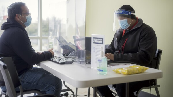 two men with face masks sit at a table