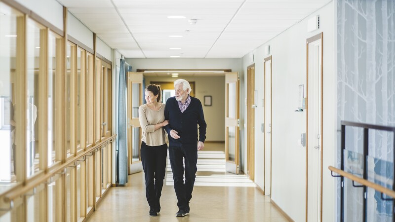 Young woman looking away while walking with grandfather in corridor at nursing home