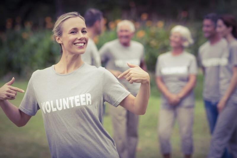 Happy volunteer showing her t-shirt to camera